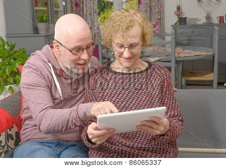 A Mother And Her Adult Son Looking At A Digital Tablet