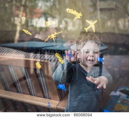 boy laughing behind a window while he is playing with stickers