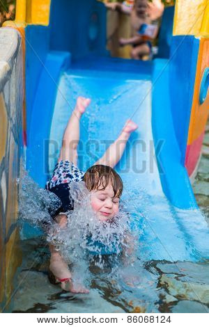boy going from the water slide splash in color