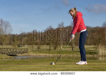 Woman Teeing Off At A Golf Course