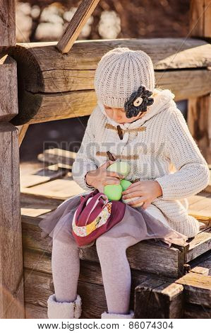cute child girl playing with easter eggs at old well