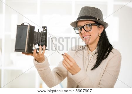 Woman with retro film camera and old suitcase