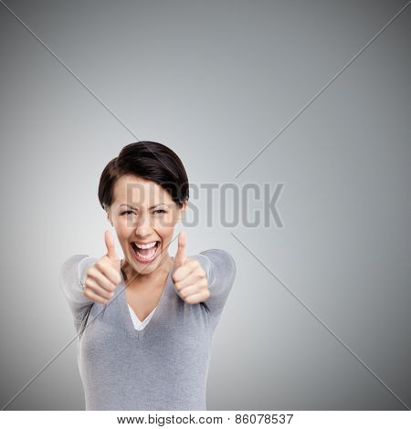 Merry girl gives thumb up, isolated on grey