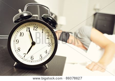 closeup of an alarm clock at 6.55 in the morning on the night table and a young caucasian man sleeping in bed with a black sleep mask