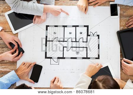 business, people, technology and team work concept - close up of architects with blueprint, smartphones and tablet pc computers sitting at table in office