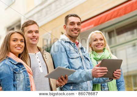 travel, vacation, technology and friendship concept - group of smiling friends with tablet pc computers in the city