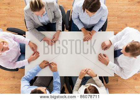 business, people and team work concept - close up of creative team sitting at table in office