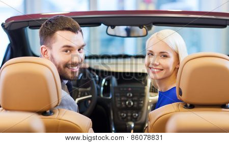 auto business, car sale, consumerism and people concept - happy couple sitting in car at auto show or salon