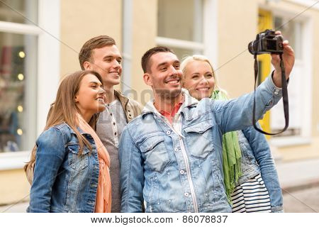 travel, vacation, technology and friendship concept - group of smiling friends making selfie with digital camera outdoors