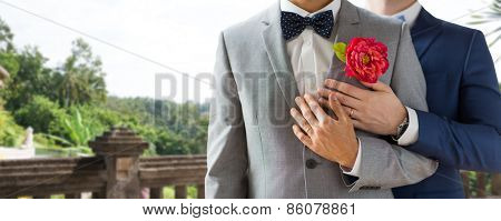 people, homosexuality, same-sex marriage and love concept - close up of happy married male gay couple in suits with buttonholes and bow-ties on wedding over balcony and nature background