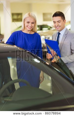 auto business, car sale, consumerism and people concept - happy woman with car dealer in auto show or salon