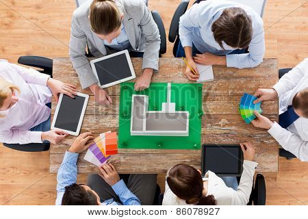 business, people and team work concept - close up of creative team with project layout, color palettes and tablet pc computers sitting at table in office