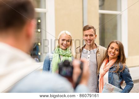travel, vacation, technology and friendship concept - guy picturing group of friends with map in city