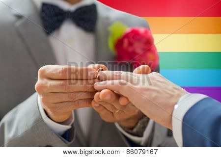 people, homosexuality, same-sex marriage and love concept - close up of happy male gay couple hands putting wedding ring on over rainbow flag background