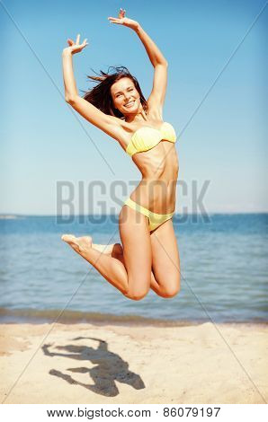 summer holidays and vacation concept - beautiful woman in bikini jumping on the beach