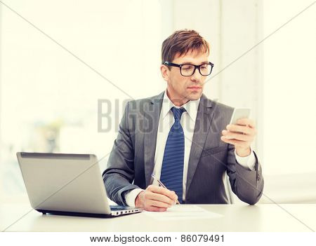 technology, business and office concept - handsome businessman working with laptop computer and smartphone