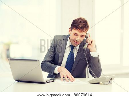 technology, business and office concept - handsome businessman working with laptop computer, phone and documents