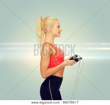 sport, exercise and healthcare concept - smiling sporty woman with skipping rope