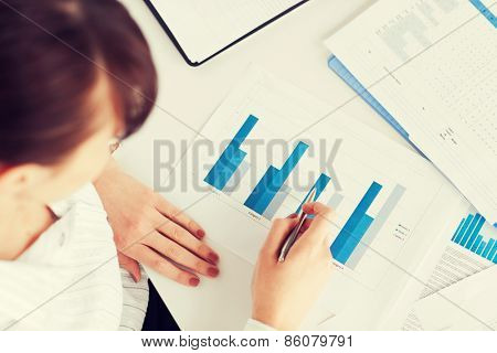 business, office, school and education concept - woman hand with charts and papers