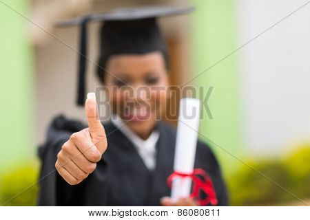 close up of young afro american graduate giving thumb up