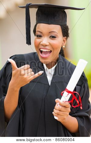 cheerful young african female graduate doing call me sign