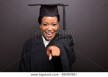 smiling female college graduate pointing isolated on black background