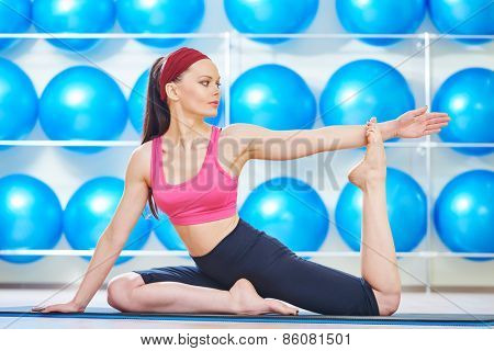 young woman instructor doing stretching pilates exercises in sport club