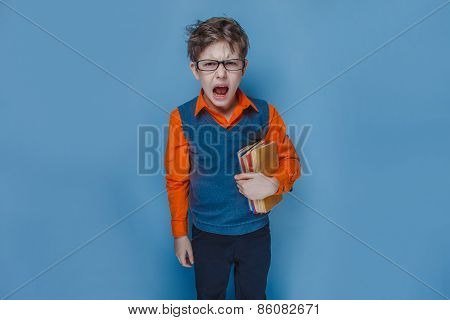 European-looking boy of ten years in glasses opened his mouth shouting holding a book on a blue back