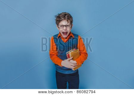 European-looking  boy of ten years in glasses opened his mouth shouting holding a book on a blue bac