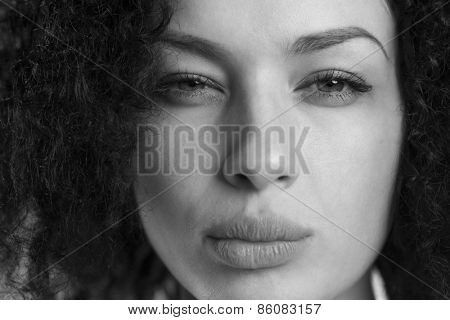Black and white portrait of a beautiful woman frowning and looking upset.