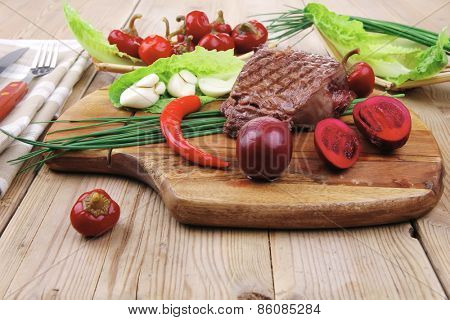 meat food : roast beef garnished with green staff and red chili hot pepper on wooden table with cutlery