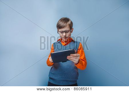 European-looking boy of ten years in glasses holding tablet in hand on blue background