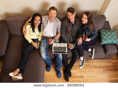 Cheerful students with laptop and drinks on a sofa