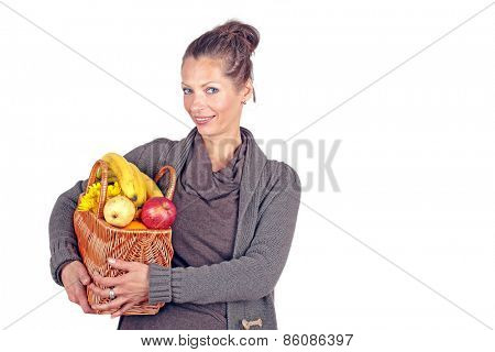 Beautiful woman coming from the market with a basket full of fruits