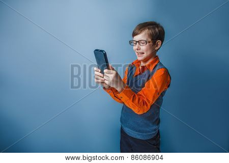 European-looking boy of ten years in glasses holding tablet in hand, plays, pleasure on a blue backg