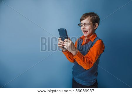 European-looking  boy of ten years in glasses holding tablet in hand, plays, pleasure on a blue back