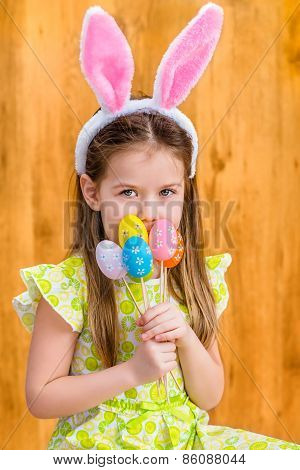 Little girl wearing pink and white rabbit or bunny ears and holding bunch of painted colorful eggs