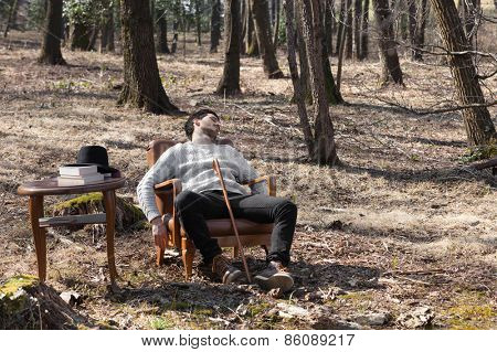 young man sleep in an armchair in the woods, portrait