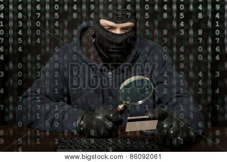 Hacker in a balaclava with laptop