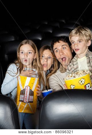 Shocked family of four with popcorn watching film in movie theater