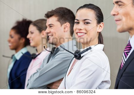 Portrait of happy female customer service representative standing with colleagues and manager at call center