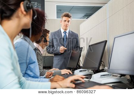 Confident manager instructing customer service representatives in office