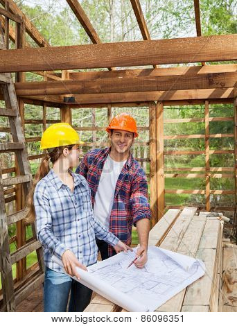 Portrait of happy male architect examining blueprint with female colleague in wooden cabin at site