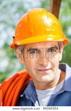 Closeup portrait of confident male construction worker wearing hardhat at site