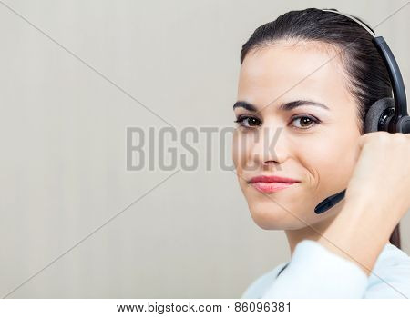 Portrait of smiling female call center employee using headset at office