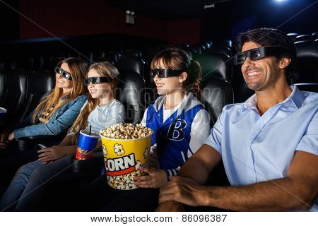 Happy family of four watching 3D movie in cinema theater