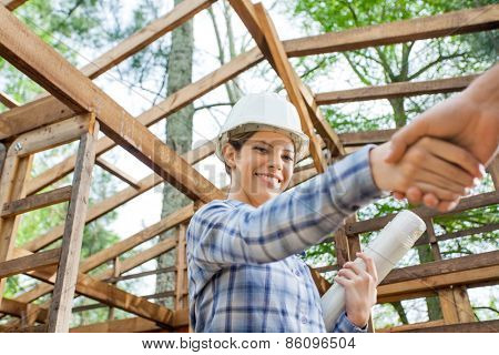 Portrait of smiling female architect greeting male colleague at construction site