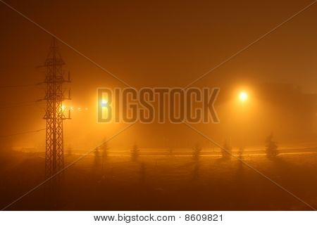 Foggy and misty urban night under yellow lights.