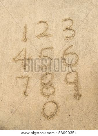Numbers from one to ten written on a sandy beach.