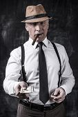 image of cigar  - Serious senior man in hat and suspenders smoking cigar and stretching out money while standing against dark background - JPG